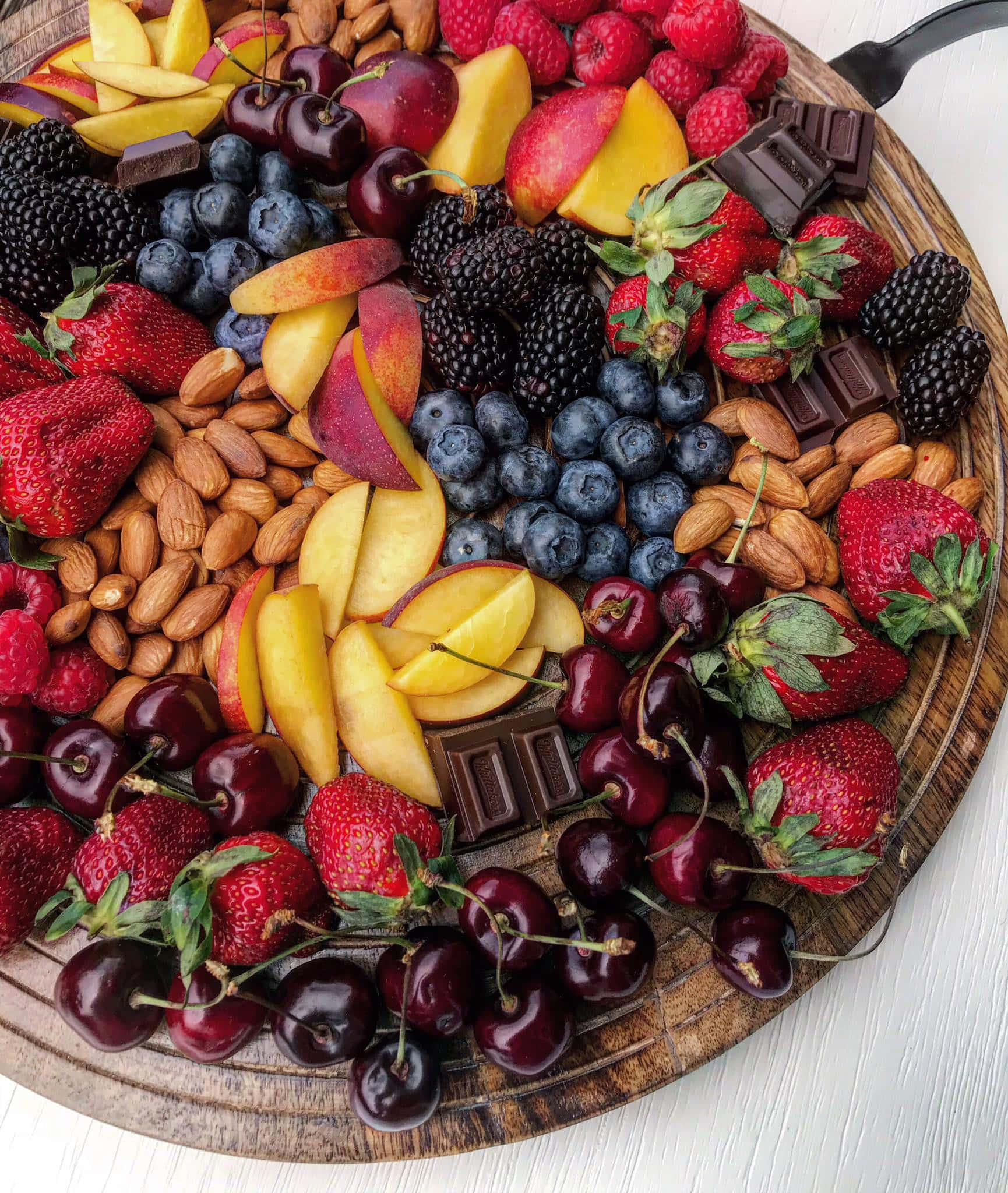 A grazing platter with summer fruit, dark chocolates and nuts
