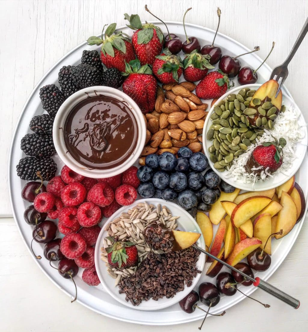 A fruit and dark chocolate fondue platter with berries, summer fruit, coconut and seeds.