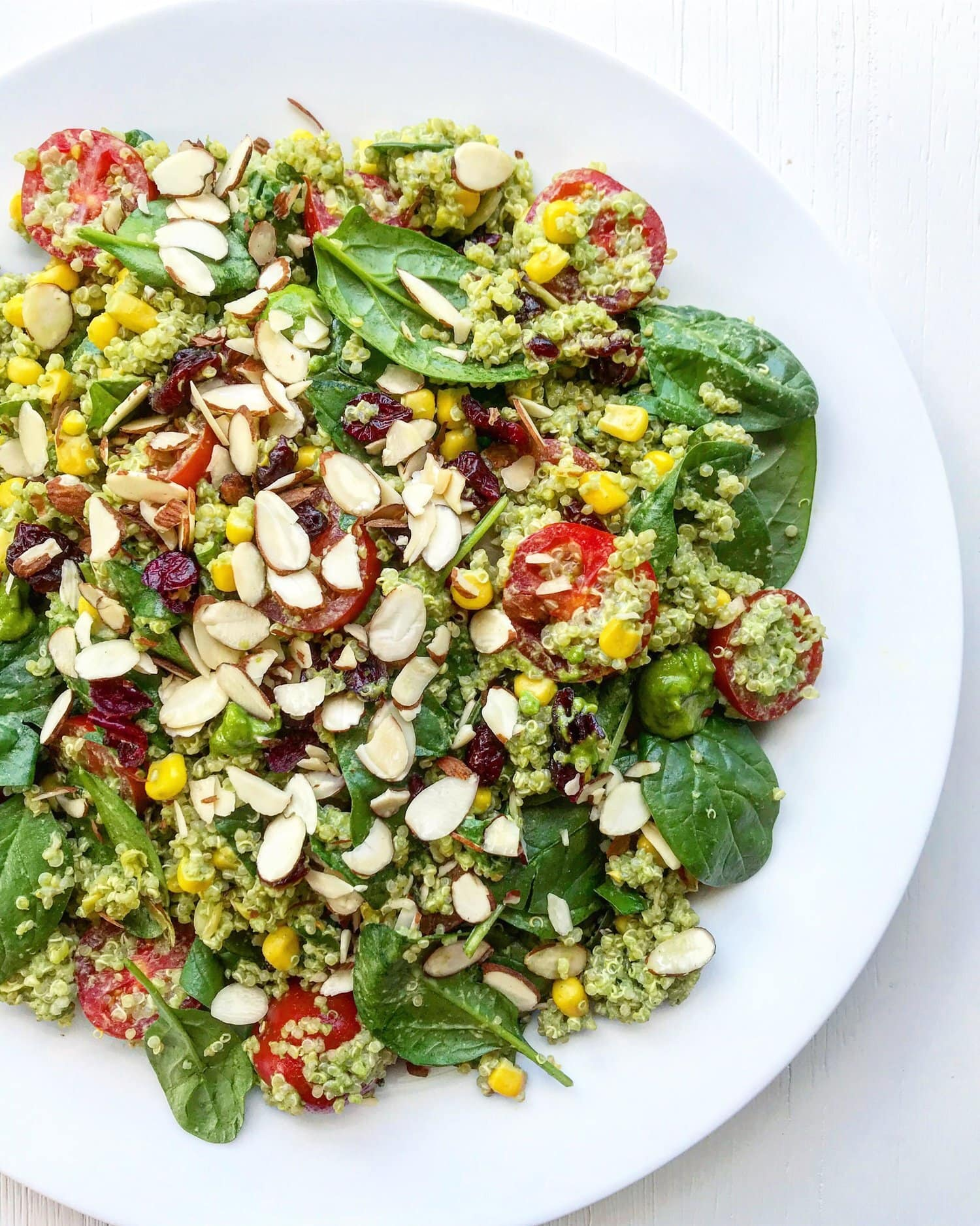 Cranberry, quinoa and pesto salad topped with flaked almonds served on a white plate.