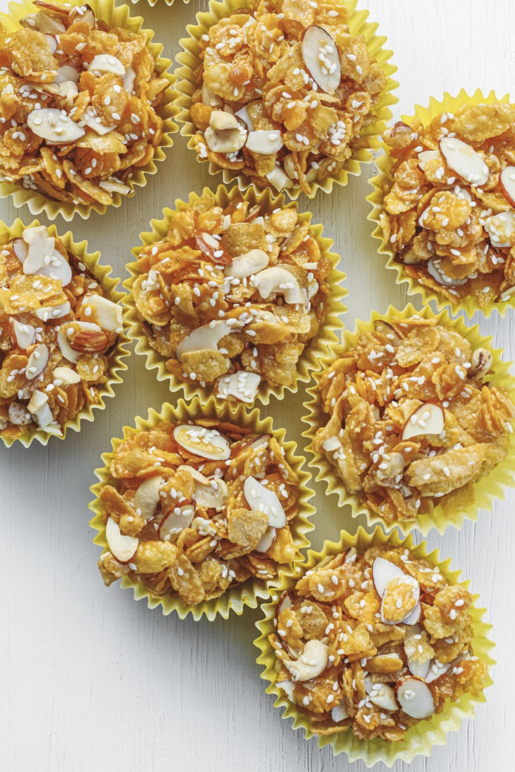 Honey joys on a white table. The honey joys are made with sliced almonds, sesame seeds, cornflakes and cashews.