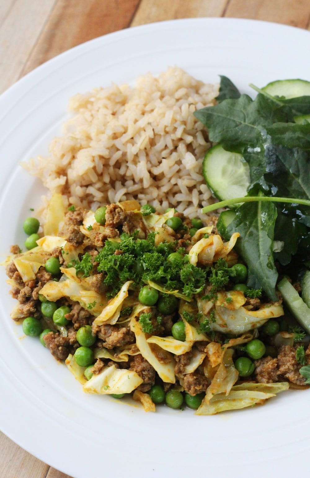 Close up of curried mince with brown rice and salad.