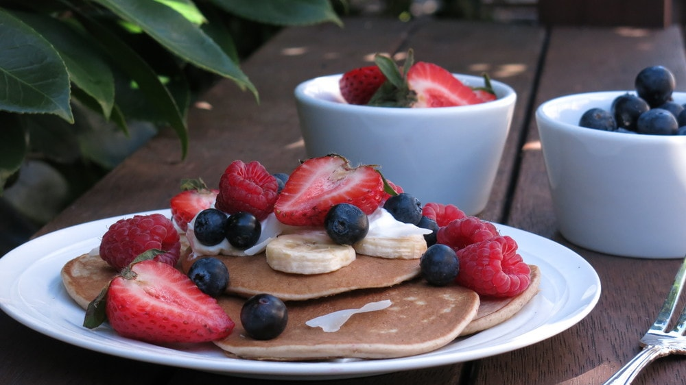 Stack of banana oat pancakes topped with fruit and yoghurt.