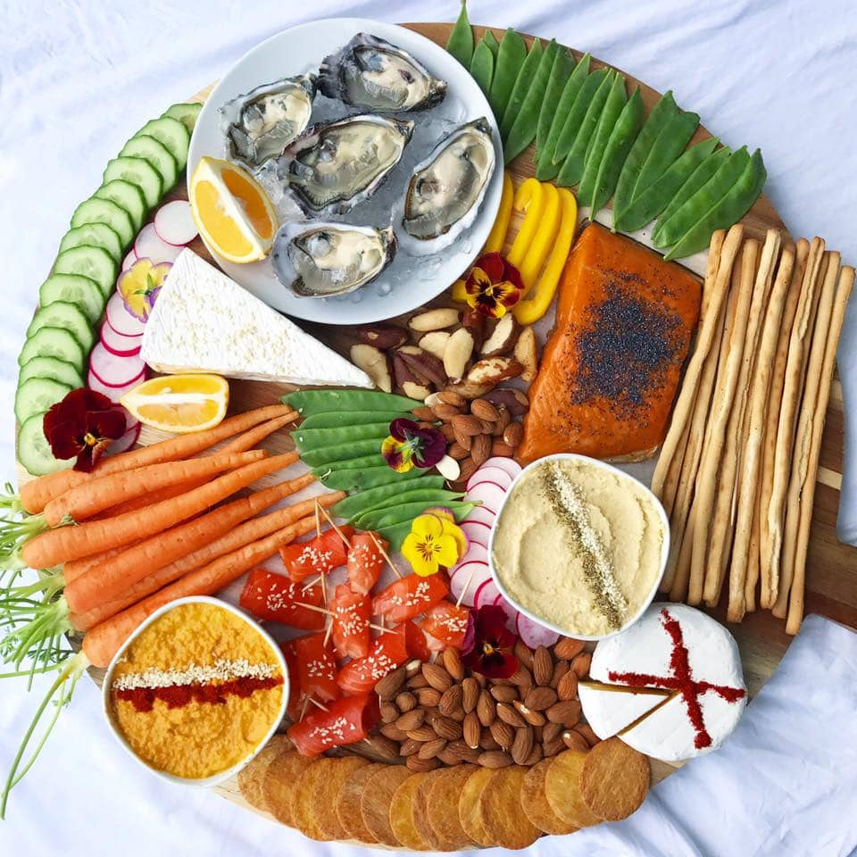 A seafood platter with oysters, smoked salmon,  fresh vegetables, dips, cheese and nuts.