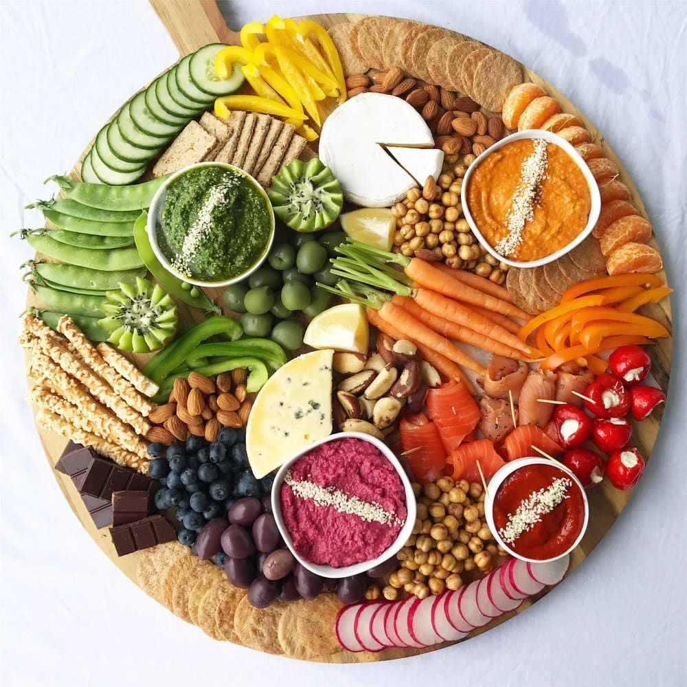 A healthy grazing platter with different dips, crackers, bread sticks, fruit and nuts.