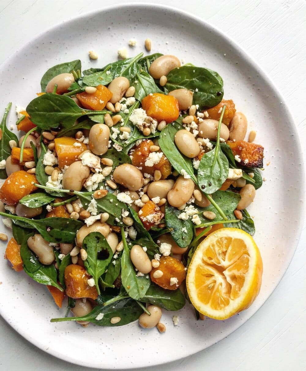 A close up of a roasted honey-pumpkin salad tossed wit spinach, white beans, feta and pine nuts. A half lemon is a garnish.