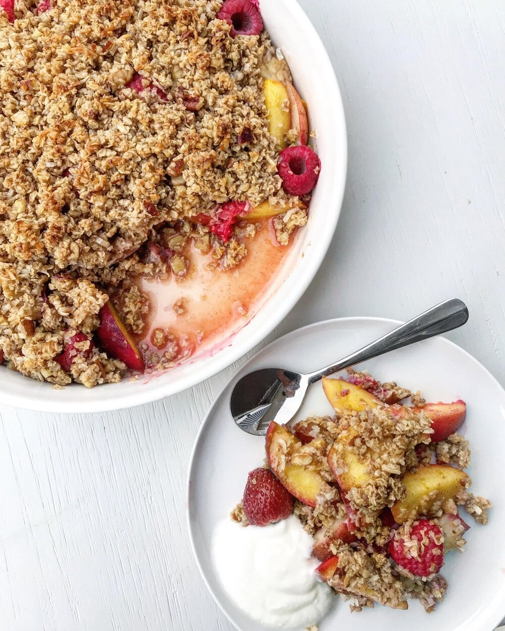 Summer berry and stone fruit crumble served on a white plate with yoghurt.