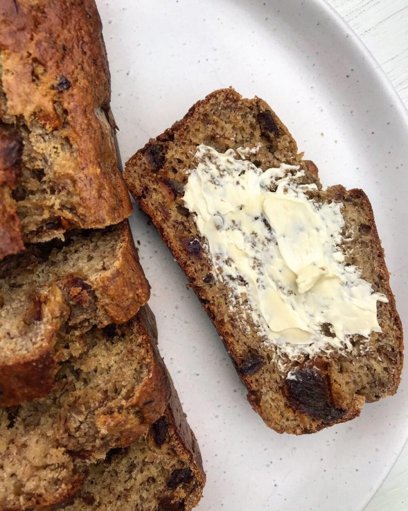 A close up of a slice of banana bread spread with butter on a white plate