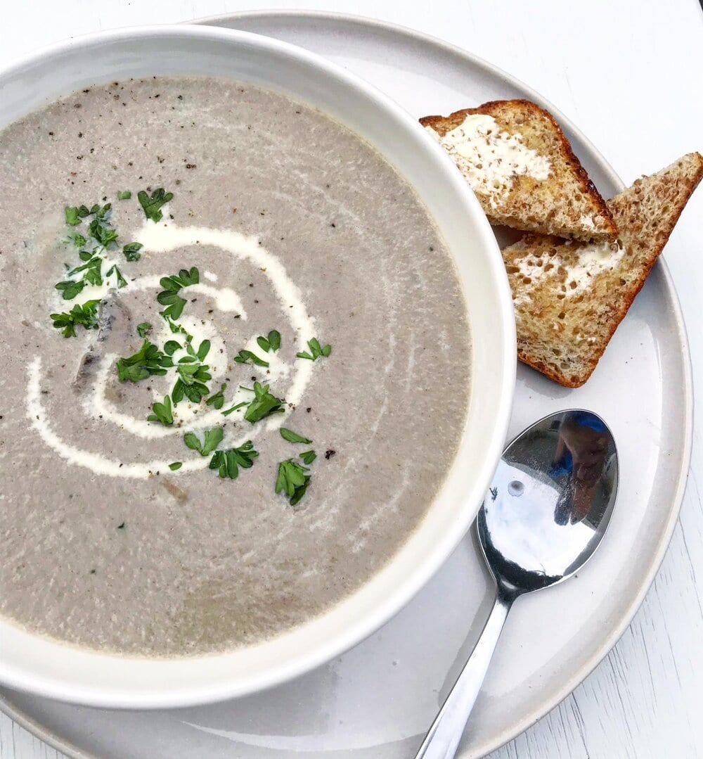 Bowl of vegan cream of mushroom soup drizzled with cashew cream, served with toast