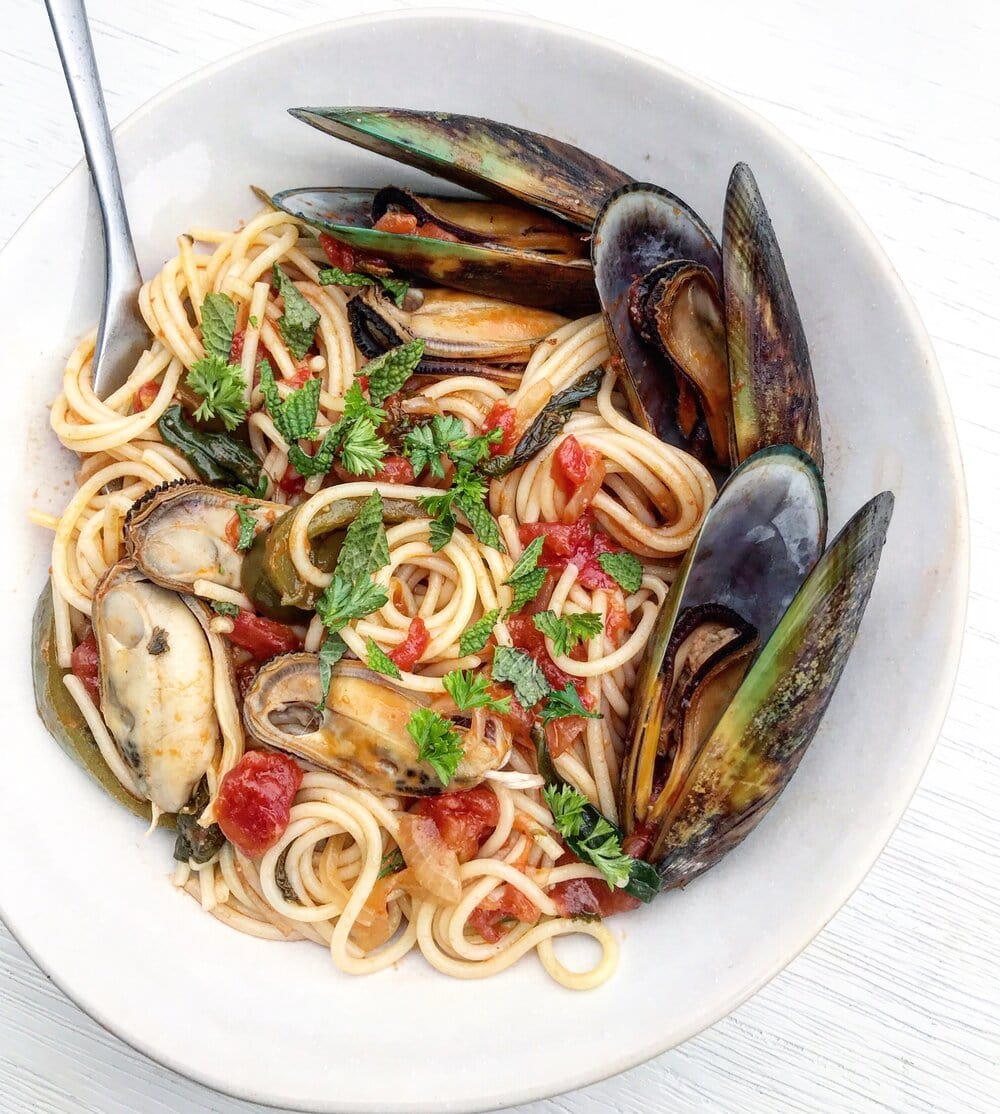 A bowl of mussel tomato pasta topped with fresh herbs.