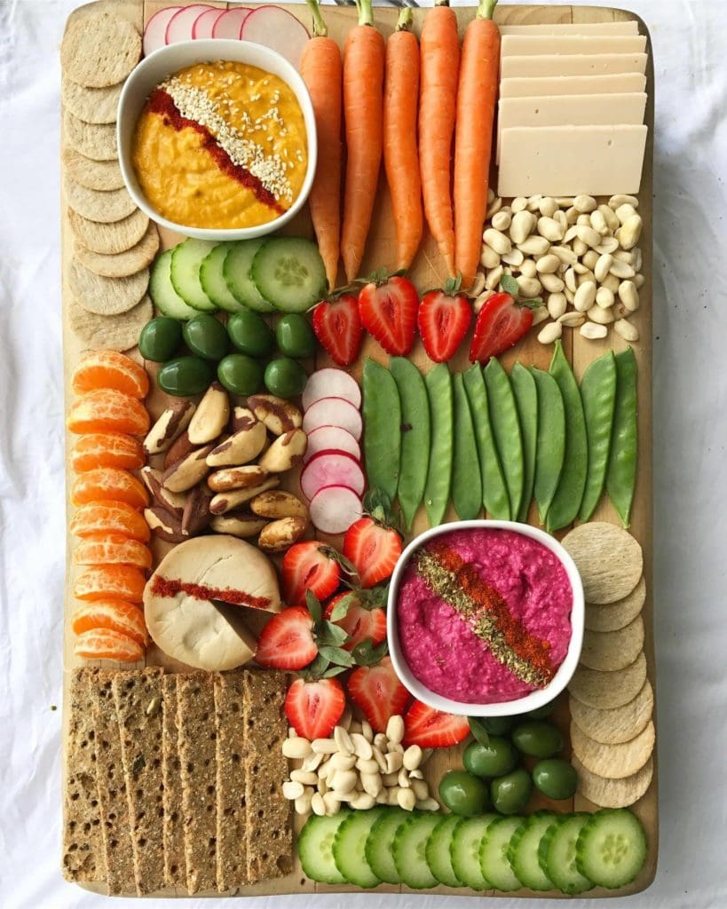 A plant-based vegan platter with fruit, vegetables, dairy-free cheeses, crackers and nuts.