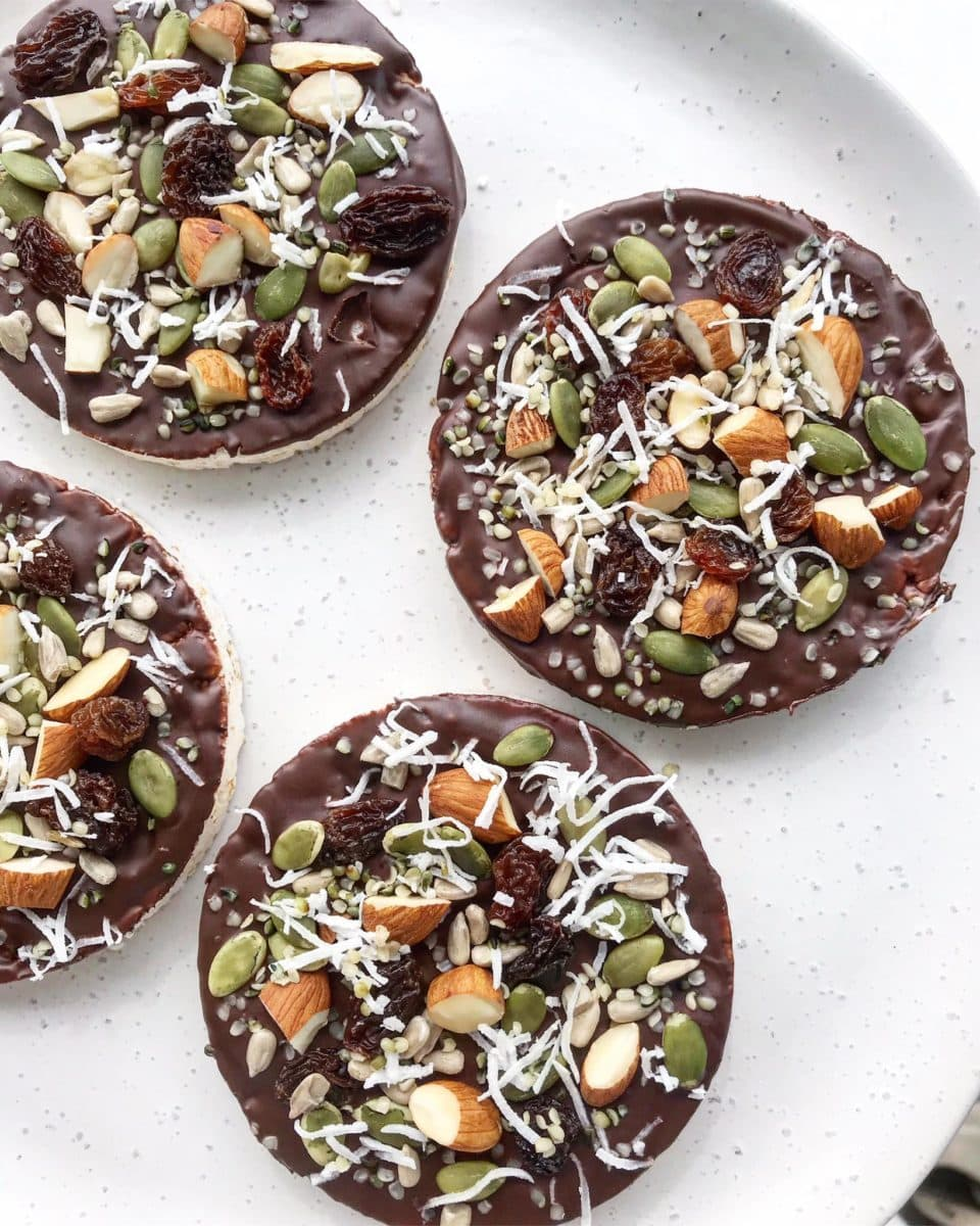 Chocolate-covered rice cakes topped with nuts, seeds and dried fruit.