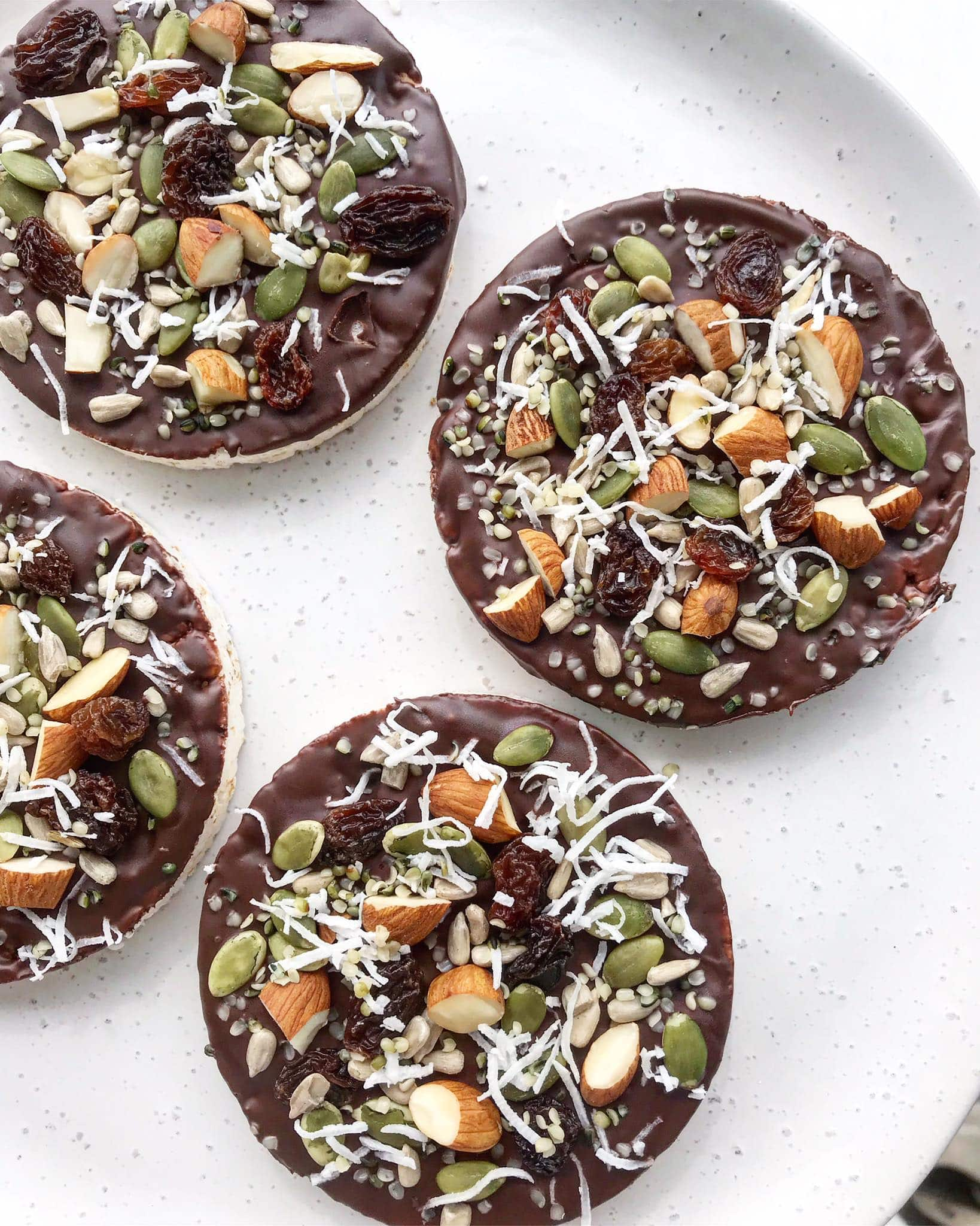 Rice cakes topped with chocolate and sprinkled with a mixture of nuts, seeds, dried fruit and coconut.