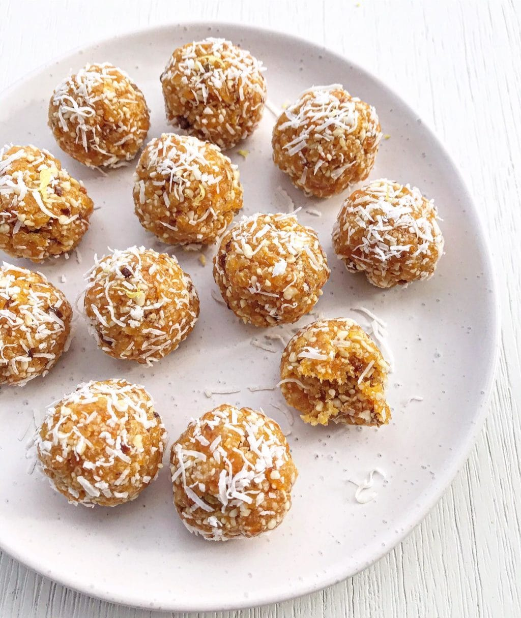 A plate of apricot and lemon bliss balls rolled in coconut.