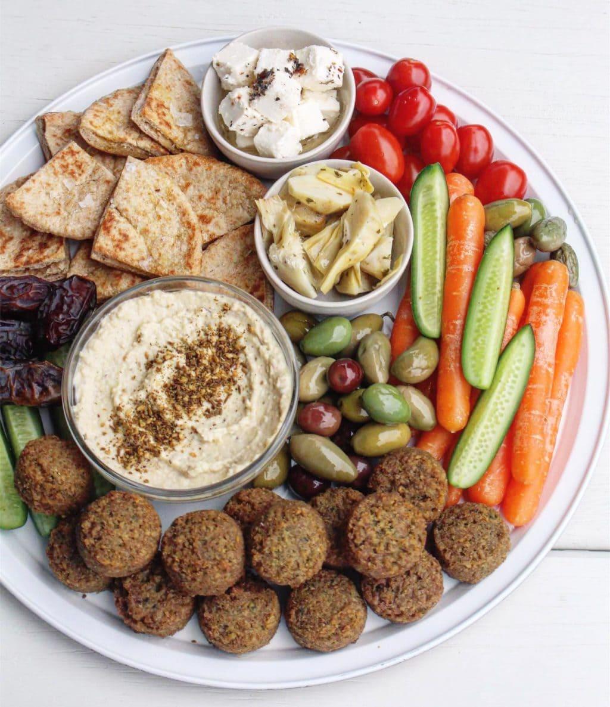 A Mediterranean grazing platter with falafel, olives, vegetable sticks, hummus, pita brea and feta.
