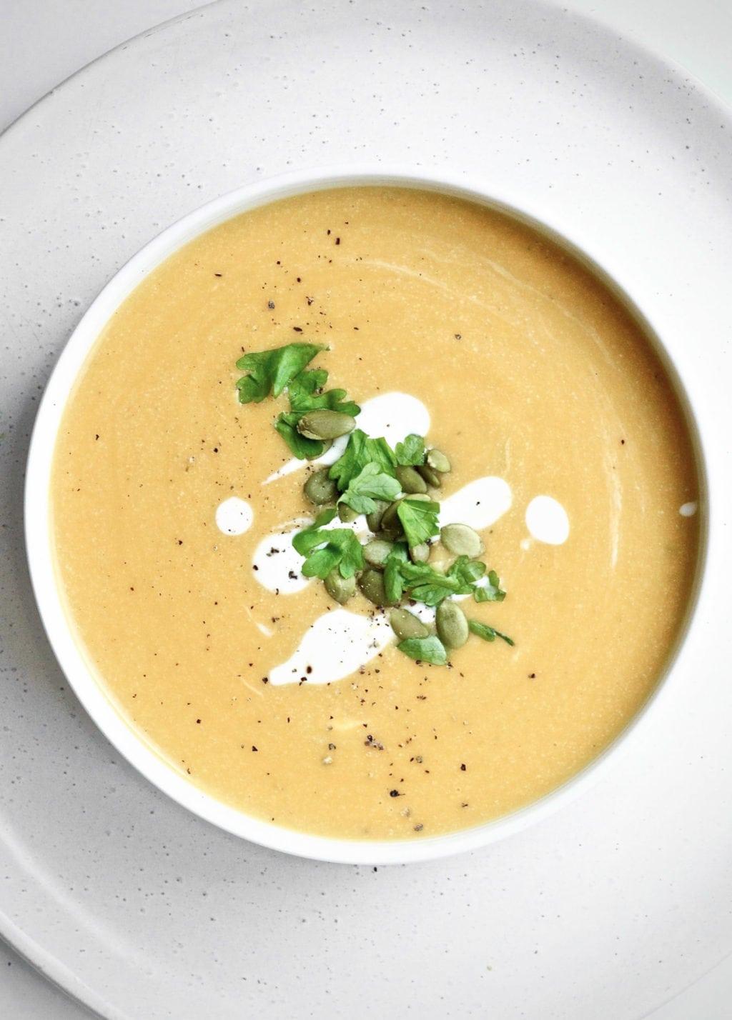 Vegan pumpkin soup garnished with cashew cream, coriander and pumpkin seeds.