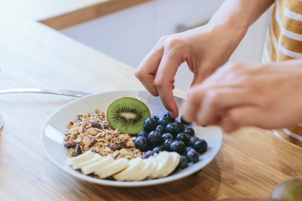 A bowl of muesli and fruit being made.